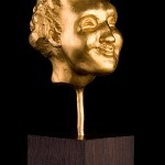 FAUN – fine gold 999, 120g, from series of grotesque heads 3.4 cm x 2.4 cm x 3.1 cm, height with plinth (ebony) 11.2 cm